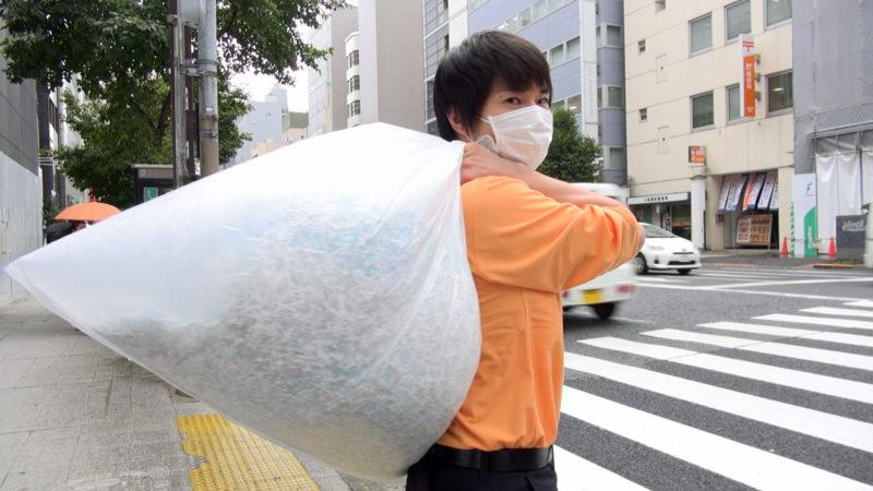 シュレッダーごみが詰められた袋を担ぎ、こちらを振り返る主人公、西村有さん(仮名)。